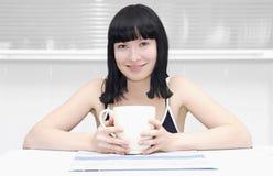 Ragazza che si siede alla cucina con una tazza Fotografia Stock