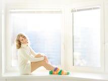 Ragazza che si siede alla finestra Immagine Stock