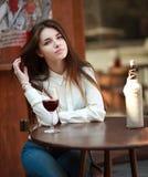 Ragazza che si siede alla tavola in caffè di estate con bicchiere di vino fotografia stock