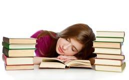 Ragazza che si siede allo scrittorio e che dorme su un libro Fotografie Stock