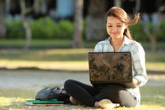 Ragazza che si siede con il computer portatile ed i libri Fotografia Stock