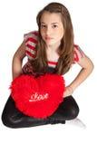 Ragazza che si siede con il cuscino a forma di del cuore Fotografia Stock Libera da Diritti