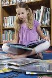 Ragazza che si siede con il libro in biblioteca Immagine Stock