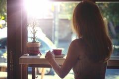Ragazza che si siede con la tazza di caffè Fotografie Stock