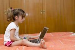 Ragazza che si siede con un computer portatile Immagini Stock Libere da Diritti