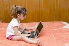 Ragazza che si siede con un computer portatile Fotografia Stock Libera da Diritti