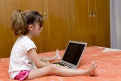 Ragazza che si siede con un computer portatile Fotografie Stock Libere da Diritti