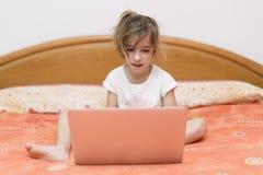 Ragazza che si siede con un computer portatile Immagini Stock