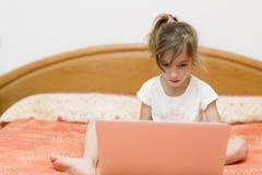 Ragazza che si siede con un computer portatile Immagine Stock Libera da Diritti