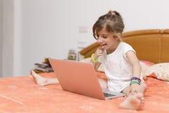 Ragazza che si siede con un computer portatile Fotografia Stock