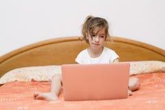 Ragazza che si siede con un computer portatile Immagine Stock