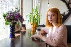 Ragazza che si siede con una tazza di caffè fotografia stock libera da diritti