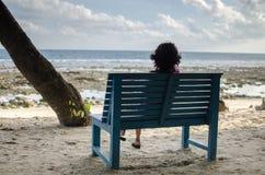 Ragazza che si siede da solo su un banco vicino alla spiaggia Fotografie Stock Libere da Diritti