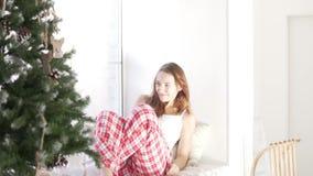 Ragazza che si siede dalla finestra all'albero di Natale decorato stock footage
