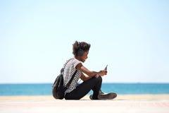Ragazza che si siede dalla spiaggia che ascolta la musica con le cuffie Immagine Stock