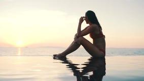 Ragazza che si siede dallo stagno sui precedenti dell'oceano al tramonto video d archivio