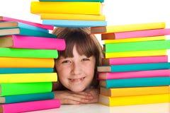 Ragazza che si siede dietro il mucchio dei libri Fotografia Stock