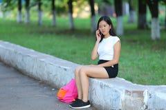 Ragazza che si siede e che parla sul telefono nel parco Immagini Stock Libere da Diritti