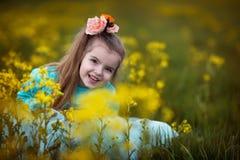 Ragazza che si siede in fiori Fotografie Stock