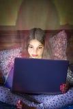 Ragazza che si siede a letto esaminando computer portatile con incandescenza intensa dallo schermo Immagine Stock
