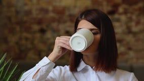 Ragazza che si siede nel caffè, cofee bevente e parlante con qualcuno stock footage