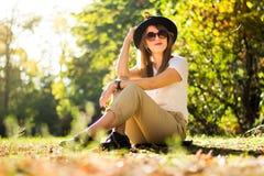 Ragazza che si siede nel parco coperto di foglie di autunno immagini stock libere da diritti