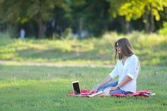 Ragazza che si siede nel parco, sorridente e lavorante al suo computer portatile Immagine Stock