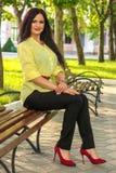 Ragazza che si siede nel parco sul banco immagini stock