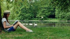 Ragazza che si siede nel parco vicino al lago sotto l'albero e che legge un libro archivi video