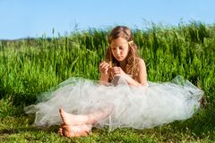 Ragazza che si siede nel prato verde Fotografia Stock Libera da Diritti