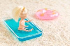 Ragazza che si siede nella piccola piscina per i bambini e che esamina il galleggiante dello stagno sull'estratto della spiaggia  fotografia stock libera da diritti