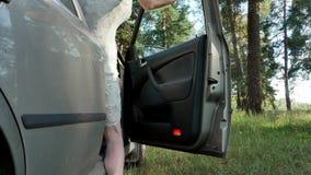 Ragazza che si siede nella porta di automobile in foresta 4k video d archivio