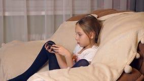 Ragazza che si siede nella sedia comoda e che esamina il telefono cellulare dello schermo video d archivio