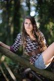 Ragazza che si siede su un albero Fotografia Stock