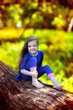 Ragazza che si siede su un albero Fotografie Stock
