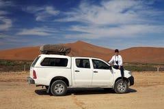 Ragazza che si siede su un'automobile fuori strada sul safari fotografico immagini stock