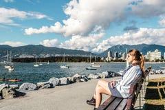 Ragazza che si siede su un banco alla spiaggia di Kitsilano a Vancouver, Canada Immagini Stock Libere da Diritti
