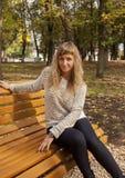 Ragazza che si siede su un banco giallo Fotografia Stock Libera da Diritti