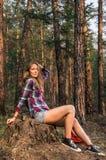 Ragazza che si siede su un ceppo nel legno Fotografia Stock Libera da Diritti
