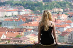Ragazza che si siede su un fondo dell'inferriata della città - Praga Fotografie Stock