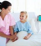 Ragazza che si siede su un letto di ospedale con il suo medico Fotografia Stock