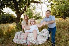 Ragazza che si siede su un'oscillazione, padre sulla madre che spinge sulla natura, famiglia felice, genitori, sorriso, gioia Fotografie Stock
