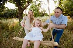 Ragazza che si siede su un'oscillazione, padre sulla madre che spinge sulla natura, famiglia felice, genitori, sorriso, gioia Fotografia Stock Libera da Diritti