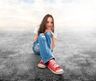 Ragazza che si siede su un pavimento Fotografia Stock