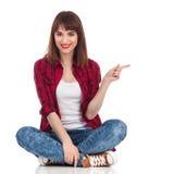 Ragazza che si siede su un pavimento e su un indicare Fotografia Stock