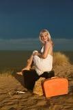 Ragazza che si siede su una valigia alla spiaggia Fotografia Stock Libera da Diritti