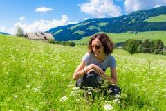 Ragazza che si siede sui fiori pieni d'ammirazione dell'erba Fotografia Stock Libera da Diritti