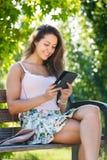Ragazza che si siede sul banco con ereader Fotografia Stock
