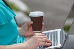 Ragazza che si siede sul banco e che per mezzo del computer portatile all'aperto con il caffè Fotografie Stock