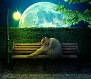 Ragazza che si siede sul banco sul grande fondo della luna Fotografia Stock Libera da Diritti